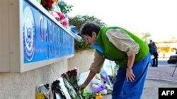 Женщина кладет цветы перед офисом члена Конгресса США Гэбриэль Гиффордс в Тусоне, штат Аризона. 8 января 2011г.