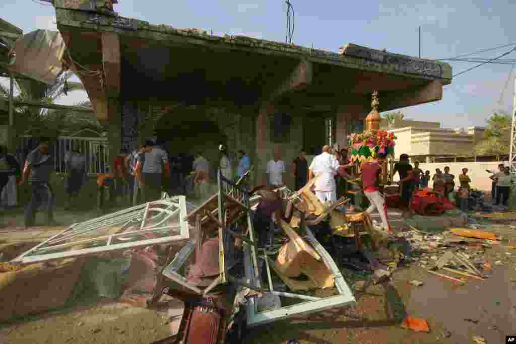Iraqis assess the damage from a bomb attack at a mosque in Hilla, about 95 kilometers south of Baghdad, Aug. 25, 2014.
