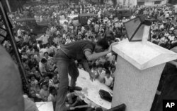 Mobs of South Vietnamese civilians scale the 14-foot wall of the U.S. Embassy in Saigon, April 29, 1975, trying to reach evacuation helicopters as the last Americans departed from Vietnam. (AP Photo)