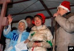 Russian human rights activist Lyudmila Alexeyeva, dressed as Snegurochka, Russian Snow Maiden, left, environmental activist Yevgenia Chirikova, center, and prominent rights activist Lev Ponomaryov speak during a rally in central Moscow, Dec. 31, 2010.