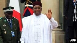 Le président nigérien Mahamadou Issoufou salue alors qu'il quitte l'Elysée après la conférence internationale sur la Libye, à Paris, le 29 mai 2018.