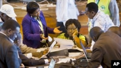 Official representatives of the various political parties and electoral workers discuss while reviewing newly received results, at the National Tallying Center in Nairobi, Kenya, Mar. 6, 2013.