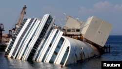 The capsized cruise liner Costa Concordia lies surrounded by cranes outside Giglio harbor, Italy, July 17, 2013.