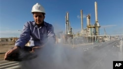 FILE - In this photo from February 2011, an employee works at an oil refinery in eastern Libya.