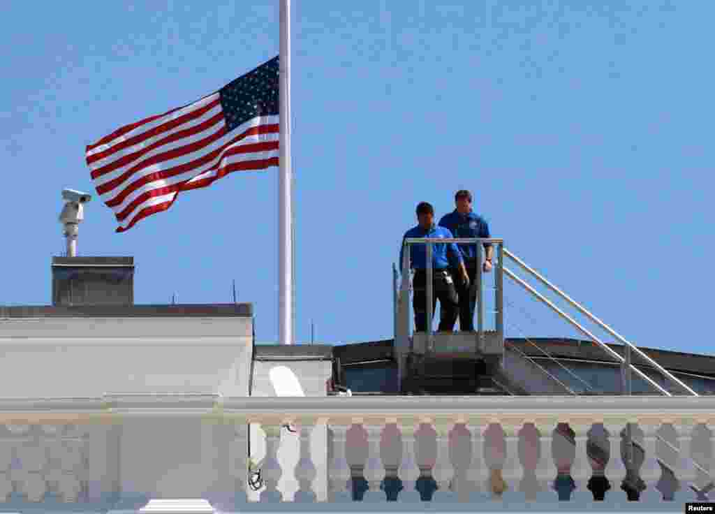 White House staff are pictured after they lowered the U.S. flag to half staff on the roof of the White House in Washington, September 12, 2012, following the death of U.S. Ambassador to Libya, Chris Stevens.