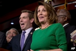 House Minority Leader Nancy Pelosi of Calif. (right) accompanied by Rep. G. K. Butterfield, D-N.C. (left) and Rep. Eric Swalwell, D-Calif. (second from left) as they joke while speaking at a news conference on Capitol Hill in Washington, March 24, 2017.