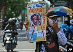 Seorang pria Muslim memegang poster Presiden Perancis Emmanuel Macron yang dicoret-coret dalam aski unjuk protes di masjid Al Jihad, Medan, Sumatera Utara, Jumat, 30 Oktober 2020.