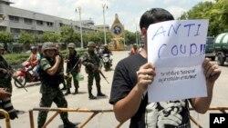 一名泰國學生星期五在曼谷街頭舉起抗議軍方的行動標語牌,表達不滿。