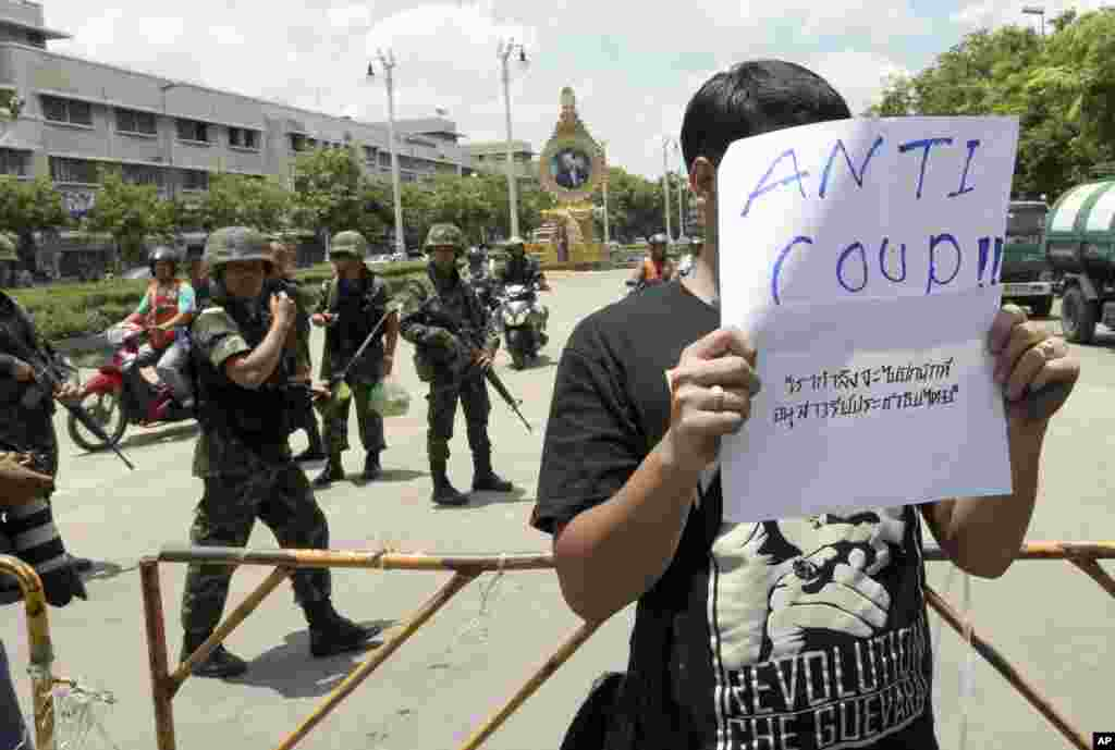 A Thai student holds an anti-coup sign in front of a group of soldiers during a brief protest near the Democracy Monument in Bangkok, May 23, 2014.