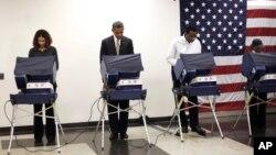 Tổng thống Obama (thứ nhì từ trái) bỏ phiếu sớm tại Trung tâm Cộng đồng Martin Luther King ở Chicago, 25/10/12