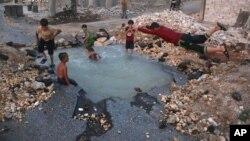 کودکان سوری در حال آب بازی در چاله ای که در اثر اثابت بمب درست شده است.