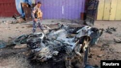 An Iraqi policeman inspects the site of a car bomb attack in Kirkuk, north of Baghdad, July 11, 2013.