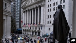 People stand near a statue of George Washington, adjacent to the New York Stock Exchange, Dec. 22, 2018, at the closed Federal Hall National Memorial in New York. A partial shutdown of the government has added another threat to a growing list of economic risks.