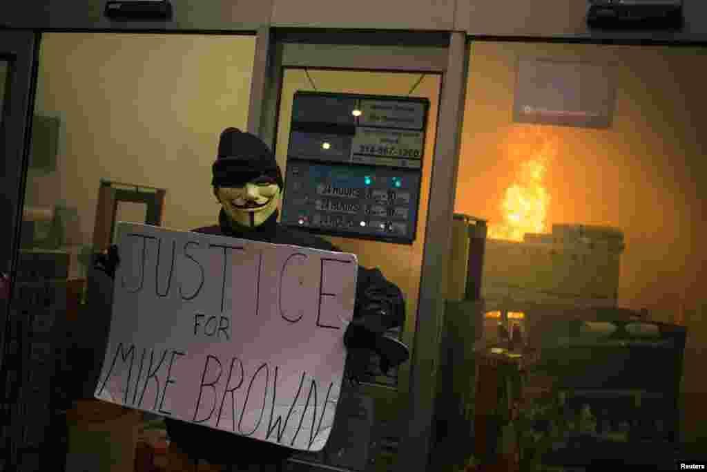 """Um manifestante segura um cartaz dizendo """"Justiça para Michael Brown"""", à porta de uma loja da cadeia de supermercados Walgreens, depois do grande júri ter anunciado a decisão de não acusar o polícia que atirou contra Micheal Brown, Ferguson, Missouri, Nov. 24, 2014."""