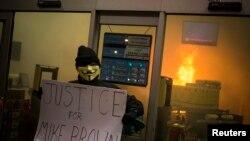Người biểu tình đứng bên ngoài một nhà thuốc Walgreens bị đốt phá tại Ferguson, Missouri, ngày 24/11/2014.