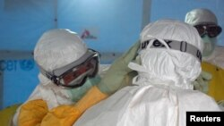 Dr. Joel Montgomery, team leader for the U.S. Centers for Disease Control and Prevention Ebola Response Team in Liberia, adjusts a colleague's personal protective equipment before entering the Ebola treatment unit in Monrovia, Liberia, Sept. 16, 2014.