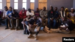 Migrants sit in the police commissioner's office after being arrested for attempting to bribe a police officer so they could pass a checkpoint without identification in Agadez, Niger, March 16, 2014.