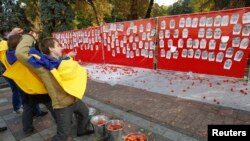 Activists throw tomatoes at portraits of parliamentary deputies, who were absent at the voting on the anti-corruption laws, outside the Ukrainian parliament in Kyiv, Oct. 7, 2014.
