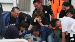 Para anggota keluarga menangisi jenazah nelayan Taiwan, Hung Shih-cheng yang tewas ditembak penjaga pantai Filipina (22/5).