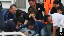Family members cry around the body of Taiwanese fisherman Hung Shih-cheng after his boat, the Kuang Ta Hsing No. 28, arrived at Liuqiu port in Pingtung County, southern Taiwan, May 11, 2013.