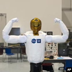 Robonaut (R2), the dexterous humanoid astronaut helper, flexes its mechanical muscles prior to its transport aboard space shuttle Discovery to the International Space Station.