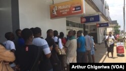 FILE: People queuing outside CBZ Bank.