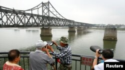 북한의 5차 핵실험 다음날인 10일 중국 졉경도시 단둥에서 사람들이 망원경으로 압록강 너머 북한 신의주 쪽을 보고 있다.