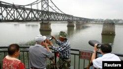 북한의 5차 핵실험 다음날인 10일 중국 졉경도시 단둥에서 사람들이 망원경으로 압록강 건너 북한 신의주 쪽을 보고 있다.