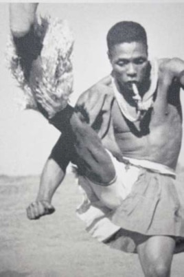A Zulu man dances while blowing a whistle on a mine near Johannesburg in this photograph taken by Hugh Tracey in the late 1940s