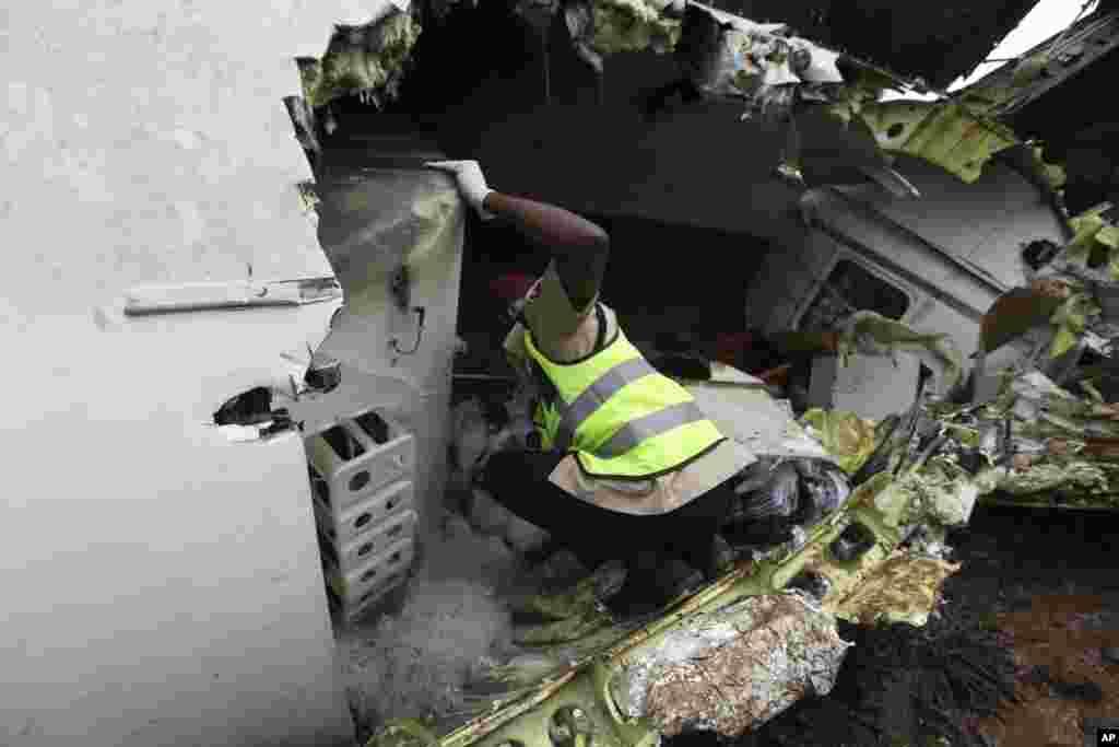 Un secouriste inspecte l'épave d'un avion de ligne qui s'est écrasé peu après son décollage de l'aéroport de Lagos, Nigeria, le 3 octobre 2013.