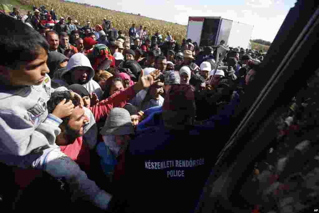Migrants in Roszke board a bus.