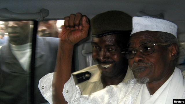 Former Chad President Hissene Habre (R) raises his fist in the air as he leaves a court in Dakar escorted by a Senegalese policeman, November 2005.