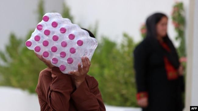 Seorang pria Afganistan membawa botol-botol air minum di sebuah kompleks penampungan pengungsi Afghanistan di Doha, Sabtu, 20 Agustus 2021.