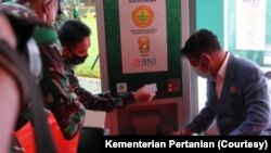 Dua orang mencoba menggunakan ATM beras. (Foto: Kementerian Pertanian)