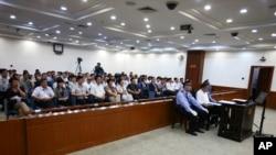在这张由山东省济南市中级人民法院公布的照片中,失势政要薄熙来在警察的左右看管下出庭接受审判。(2013年8月22日)