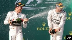 Pebalap Nico Rosberg (kiri) menyemprotkan sampanye ke teman satu timnya, Lewis Hamilton setelah memenangkan gelar GP Monaco Minggu (24/5).