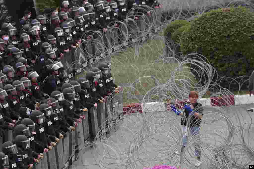Riot police stand guard as a protester attempts to get through barbed wire barricading the base entrance of the 11th Infantry Regiment, a palace security unit under direct command of the Thai king, in Bangkok, Thailand.