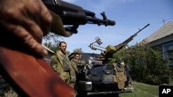 Rebeldes prorrusos vigilan cerca de una pieza de artillería en Donetsk, Ucrania.