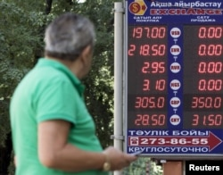 A man walks past a board showing currency exchange rates in Almaty, Kazakhstan, Aug. 20, 2015.