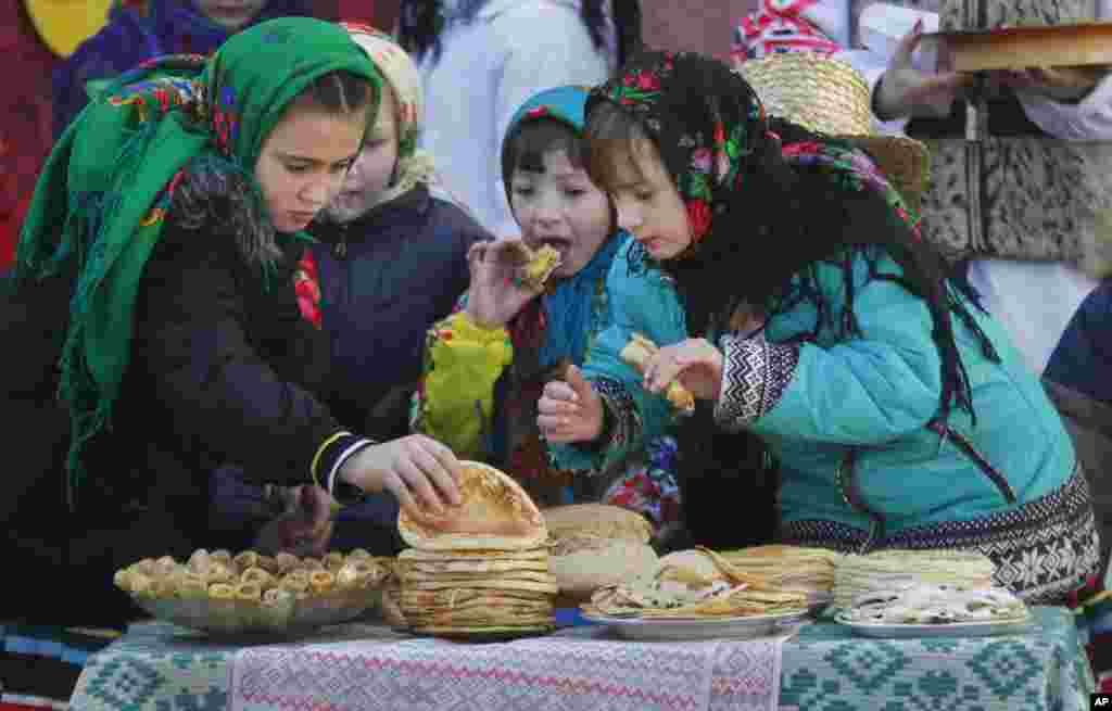 در حاشیه یک مراسم مذهبی، این دختران بلاروس، شیرینی می خورند.