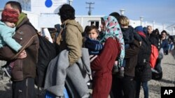 Refugees wait in line for their documents to be checked by the Greek police before they cross the borderline to Macedonia near the northern Greek village of Idomeni, on Sunday, Feb. 21, 2016. Macedonia has closed its southern border with Greece to Afghan migrants, allowing only Iraqis and Syrians, Greek police report. (AP Photo/Giannis Papanikos)