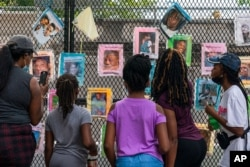 FILE - Melissa Brooks, from left, Jordan Brown, Jazmine Brooks, Shari Moore and and Laila Brooks, all of Baltimore, study photographs of Black people killed by police that cover a fence near the White House, Washington, Aug. 25, 2020.