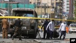 Petugas medis mengangkut jenazah korban tewas dalam ledakan pada sebuah minibus di Kabul, Afghanistan, Senin (3/6).