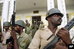 FILE - Haitian soldiers stand guard outside the military headquarters in Port-au-Prince, Haiti, Sept. 18, 1994.