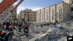 Syrian workers inspect the site of an explosion outside a military security building, one of two sites of bomb blasts in Syria's northern city of Aleppo, February 10, 2012.