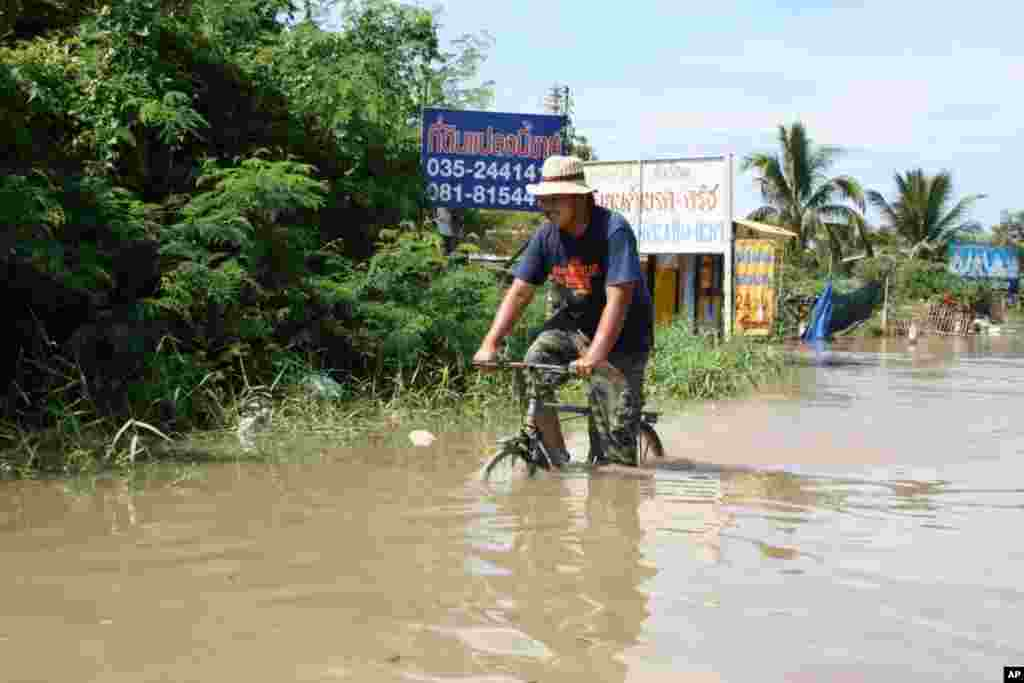 Man bikes on a flooded road in Ayutthaya, October 6, 2011 (VOA - D. Schearf)