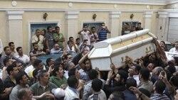 مسیحیان مصر تابوت یکی از قربانیان درگیری های شنبه با مسلمانان در غرب قاهره را در مراسم تشییع پیکر قربانیان خشونت های فرقه ای آن کشورحمل می کنند