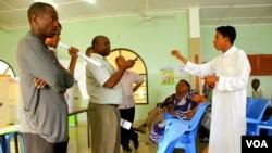 A political candidate discusses elections procedures with IEBC representatives in Mombasa, Kenya, Feb. 18, 2013. (Jill Craig/VOA)