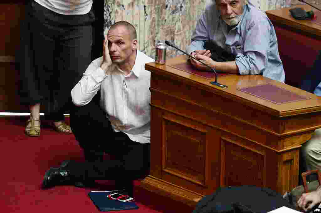 Greek Finance Minister Yianis Varoufakis (L) listens to Prime Minister addressing at the Greek Parliament in Athens.