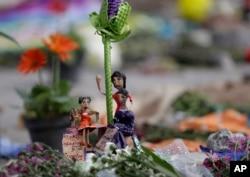 """Figuras de mujeres con una leyenda que dice: """"Unidas en solidaridad y fuertes"""" son parte de una ofrenda en una fábrica textil que se derrumbó la semana pasada en el terremoto de 7,1 que estremeció a México. Sept. 25, 2017."""